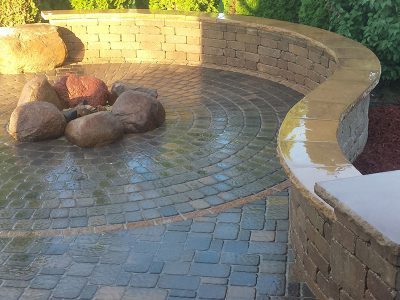 Patio designed with a stone fire pit and stone seating wall.