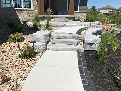 Landscape lighting on a custom stone walkway in residential landscaping.
