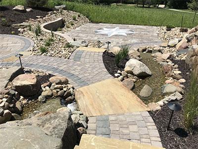 Landscaping lighting illuminates a brick and stone path and a custom patio design.